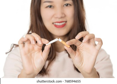 Beautiful Asian woman smiling while breaking a cigarette to quit smoking isolated on a white background