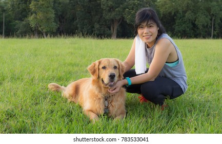 Beautiful Asian Woman in Sport Wear with Her Golden Dog are Sitting for Relax in The Field.