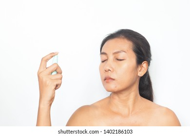 Beautiful Asian woman spraying mineral water on her face. Beauty and health concept
