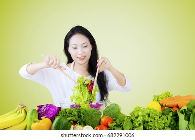 Beautiful Asian woman stirring a bowl of fresh vegetable salad, shot with green screen background