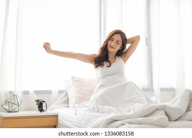 Beautiful Asian woman stretching her arms in bed on early morning on holiday.