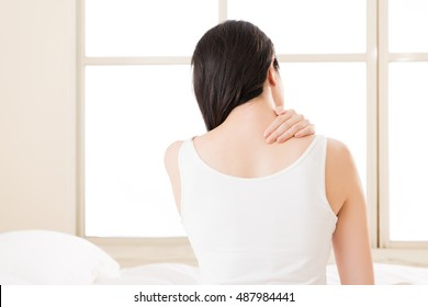 Beautiful asian woman suffering Shoulder neck ache tired sit on bed. bedroom background. back view