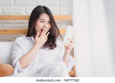 Beautiful Asian woman surprised and shocked while looking in smartphone mobile on the bed in the morning after wake up