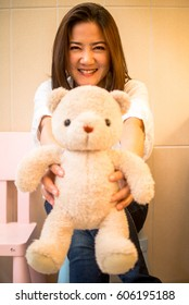 Beautiful Asian woman with the sweet smile in studio incandescent light  with teddy bear , focus on model face.