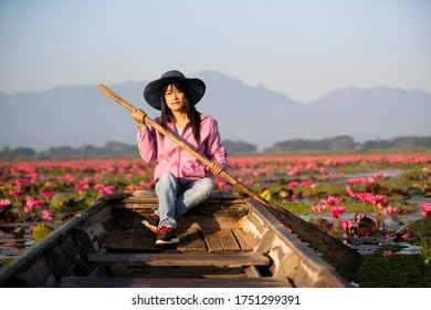 beautiful asian woman Take a boat to admire the beauty Landscape red Lotus in the morning background,At a lake in Phayao Province of Thailand