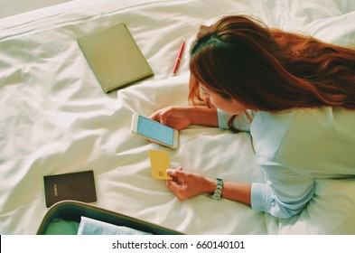 Beautiful Asian woman take a rest on bed and using smart phone