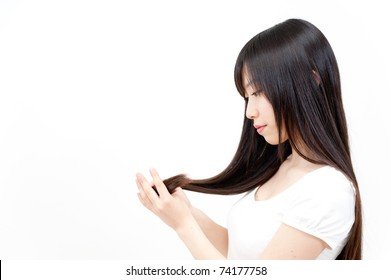 beautiful asian woman taking care of long straight hair