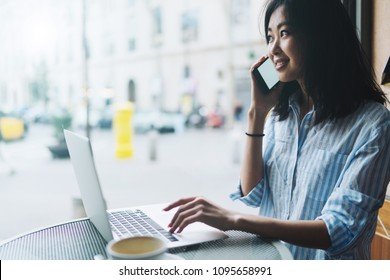 Beautiful asian woman is talking by a mobile phone while sitting in a coffee shop with a laptop. Young freelancer girl is calling to the clients and reading emails on a portable computer.