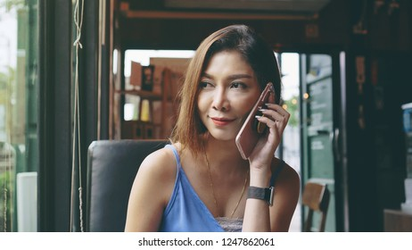 Beautiful asian woman talking on the mobile phone with boyfriend in cafe