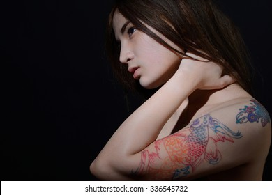 Beautiful asian woman with tattoo on her arm and shoulder,dark background
