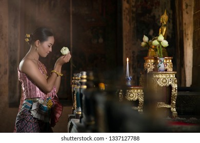 The beautiful asian woman in the Thai national costume is paying homage to the Buddha image with lotus flowers and prayers in the temple.