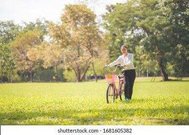 A beautiful Asian woman, Thai woman, is walking on a bicycle in a beautiful public place in the morning with a fresh and smiling face. Concept of exercise on a clear day