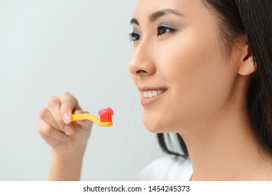 Beautiful Asian woman with toothbrush and paste on light background