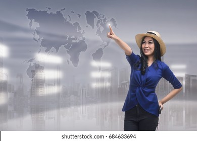 Beautiful asian woman touching travel destination on virtual screen over futuristic background