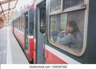 A beautiful Asian woman travel by train (Alishan forest railway line) to Alishan mountain in Taiwan.
