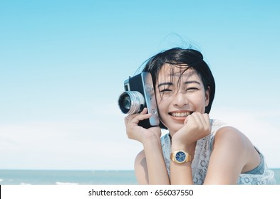 Beautiful Asian woman traveling at beach with vintage camera in hand