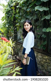 Beautiful asian woman in tropical garden holding a book with her hands, standing at live wall outside stone house. Girl and the book. Novel writer.