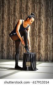 Beautiful Asian woman tying her shoes, preparing for ballet class.