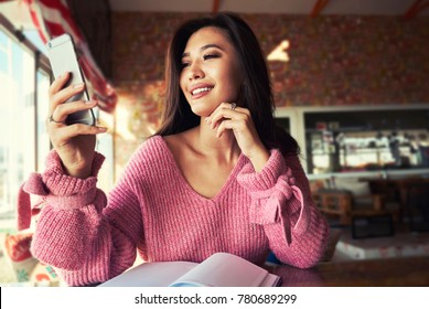 Beautiful  asian woman using an application to send an sms message in her smartphone device while sitting in modern coffee shop.