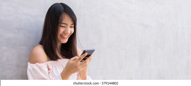 Beautiful asian woman using cellphone, over concrete wall. Panoramic banner.