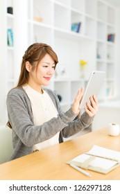 Beautiful asian woman using a ebook