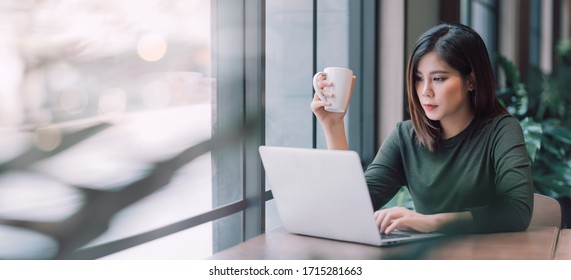 Beautiful Asian Woman Using Laptop Computer Online Working from Home ,  E-Learning , Online Shopping , E-Commerce , Freelance Concept - Healthcare and Social Distancing Concept