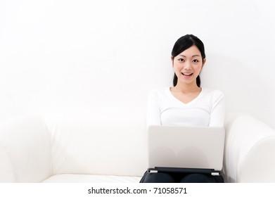 beautiful asian woman using laptop computer on the sofa