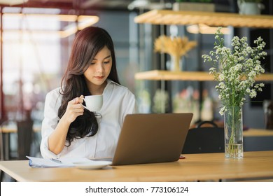 Beautiful asian woman using laptop at cafe while drinking coffee, Relaxing holiday concept.