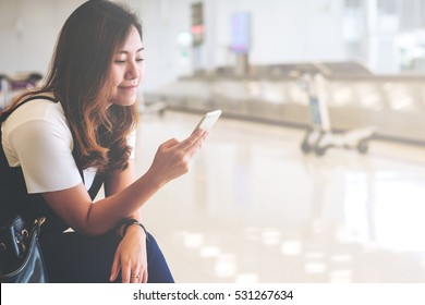 A beautiful asian woman using mobile phone with feeling happy and smiley face , sitting and waiting for baggage claim in blur airport background