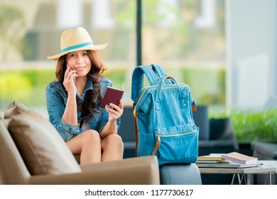 Beautiful asian woman using mobilephone with feeling happy and smiley face , sitting and waiting for her flight in blur airport background
