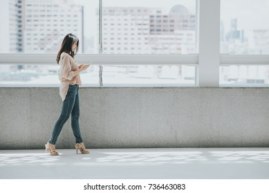 Beautiful Asian woman using smartphone for texting while walking in modern office building