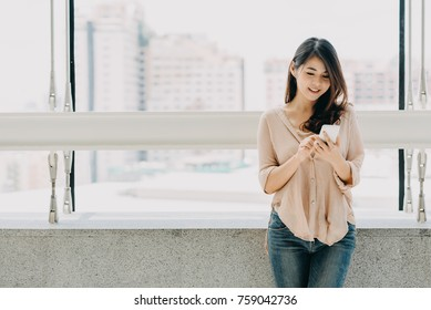 Beautiful Asian woman using smartphone in modern office building