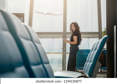 Beautiful asian woman using tablet computer waiting at gate area interior with seats and windows in airport terminal with airplane on background. Copy space