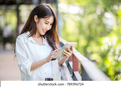 Beautiful Asian woman using tablet computer outdoor in the city to complete her own business. Online business concept