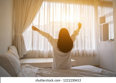 Beautiful Asian woman waking up on her bed in the bedroom, she is stretching and smiling after wake up, Asia women exercising in the morning, feels refreshed.good dream last night, lifestyle in home