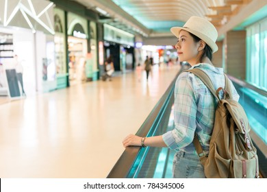 beautiful Asian woman walking around airport. looking window shopping of the duty free shop on the escalator conveyor belt.