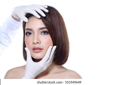 Beautiful Asian woman want to check eye, nose, eyebrow, forehead, cheek, jawline before plastic surgery, studio lighting white background copy space for text logo