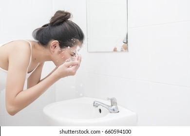 Beautiful asian woman is washing her face