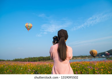 Beautiful asian woman watching colorful hot air balloons flying over field of flowers and take photo of balloon