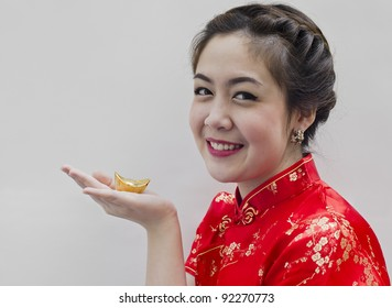Beautiful asian woman wear cheongsam and holding chinese gold ingot