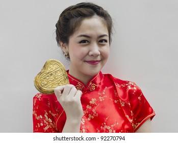 Beautiful asian woman wear cheongsam and holding golden heart