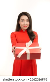 Beautiful Asian woman wear red ao dai dress, happy smile hold new year gift box present, in isolated on white background