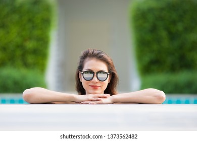 Beautiful Asian woman wear sunglasses standing in blue water pool with relax manner, pose and looking to camera with self confident.