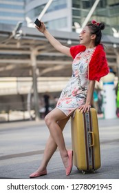 Beautiful Asian woman wearing a Chinese dress, sitting on a suitcase and using a mobile phone selfie.