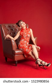Beautiful Asian woman wearing Chinese traditional red dress sitting on the sofa on red background, isolated.