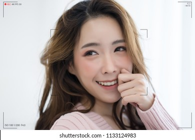 Beautiful Asian woman wearing knitted sweater pink make selfie recording video vlog from hands with mirrorless camera. Camera screen of winter girl vlogging smiling on live stream at white room.