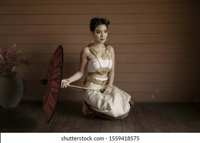 Beautiful asian woman wearing native Thai traditional dress sitting on wooden old house holding red umbrella looking out.