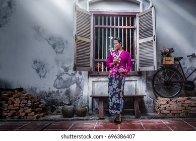 Beautiful Asian woman wearing Nyonya dress her hand holding plastic flower with old house, The dress of Paranakan woman in southeast Asia, Chinese Malay mix Traditional costume, Ranong Thailand