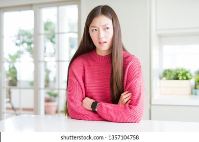 Beautiful Asian woman wearing pink sweater on white table skeptic and nervous, disapproving expression on face with crossed arms. Negative person.