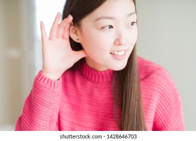Beautiful Asian woman wearing pink sweater smiling with hand over ear listening an hearing to rumor or gossip. Deafness concept.